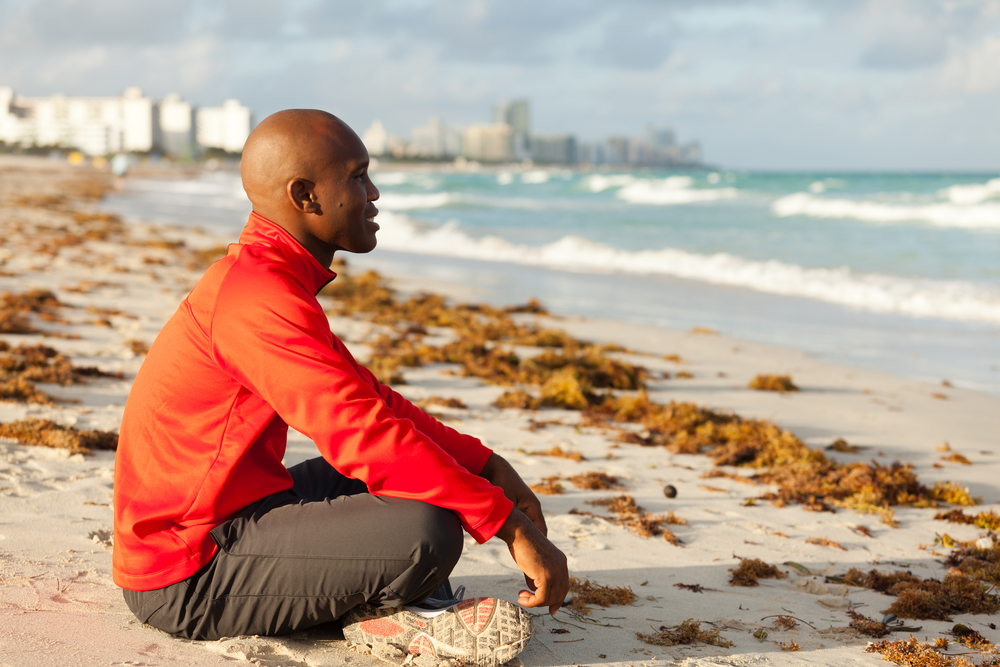 Man meditating on the beach