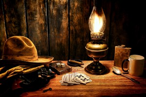 A table with a deck of cards, cowboy hat and mug.